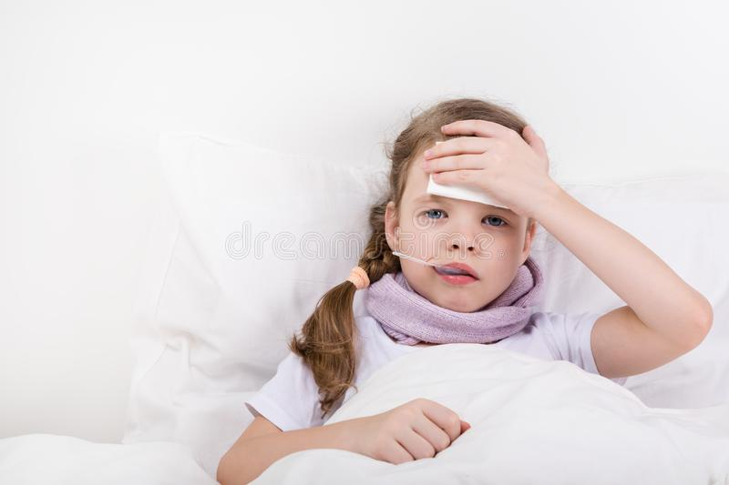 The girl is lying on the bed and her head hurts stock photo