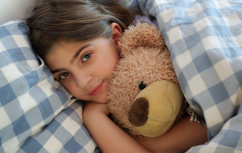 Girl Lying in Bed Hugging Her Teddybear royalty free stock photo