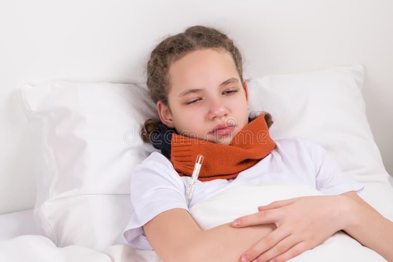 girl lying in bed, measuring body temperature with thermometer royalty free stock photo