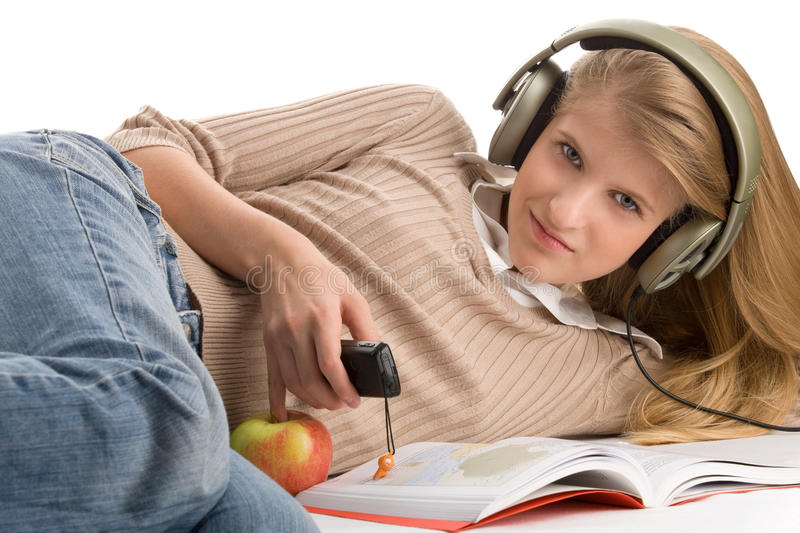 Girl lying on bed using cell phone. Pretty blond teenage girl lying on bed using cell phone and listening to music royalty free stock images