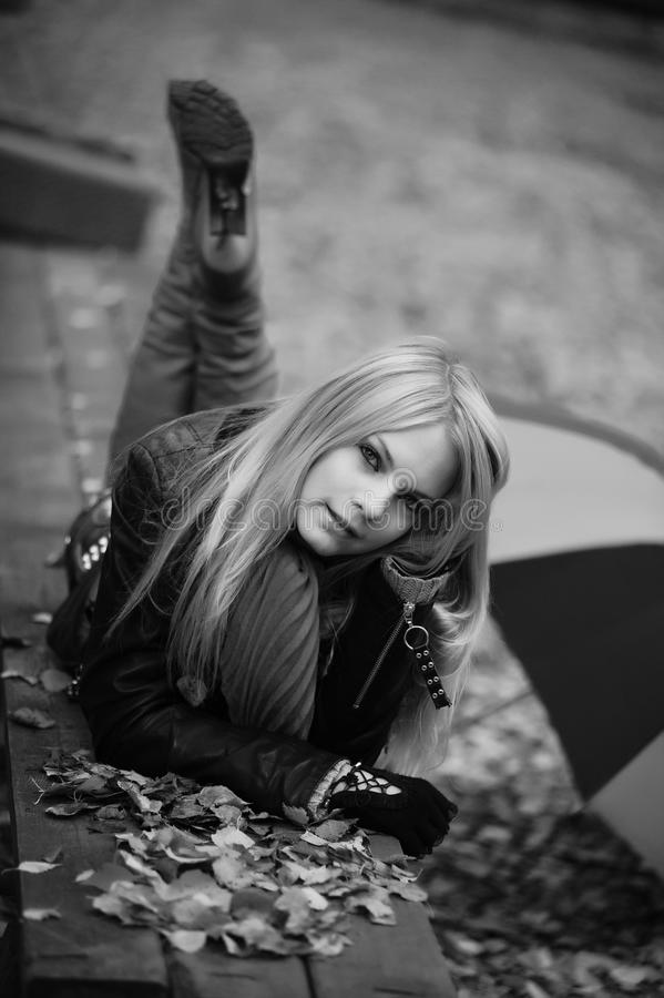 Girl lying on a bench royalty free stock photos