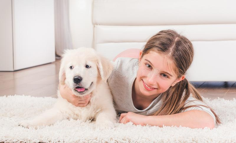 Girl lying with cute fluffy retriever puppy hugging stock image