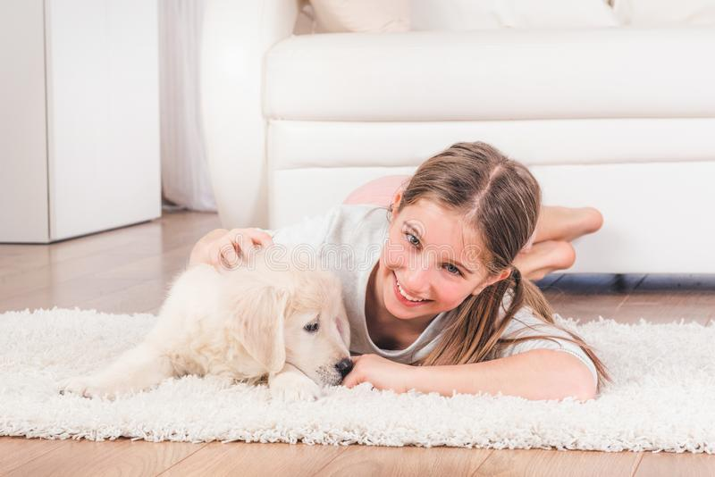 Girl lying with cute fluffy retriever puppy hugging. Smiling girl lying with cute fluffy retriever puppy hugging on carpet stock image