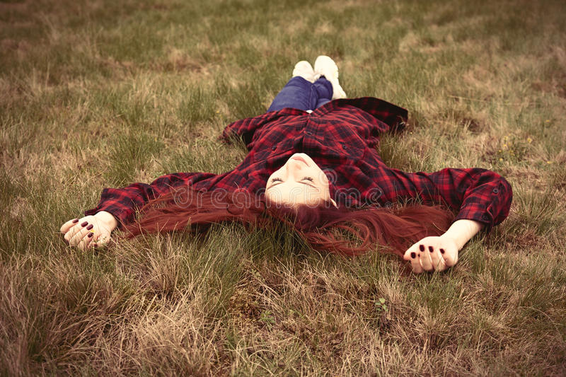 Girl lying down on the grass royalty free stock photo