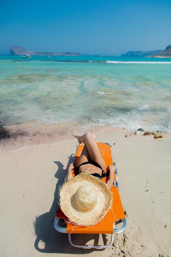 Girl lying down on lounger on Balos beach. Young redhead girl in black bikini and with hat lying down on lounger on Balos beach, west Crete, Greece. Summertime stock image