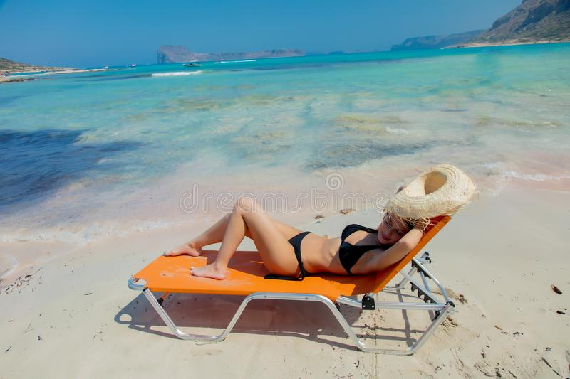 Girl lying down on lounger on Balos beach. Young redhead girl in black bikini and with hat lying down on lounger on Balos beach, west Crete, Greece. Summertime stock photos