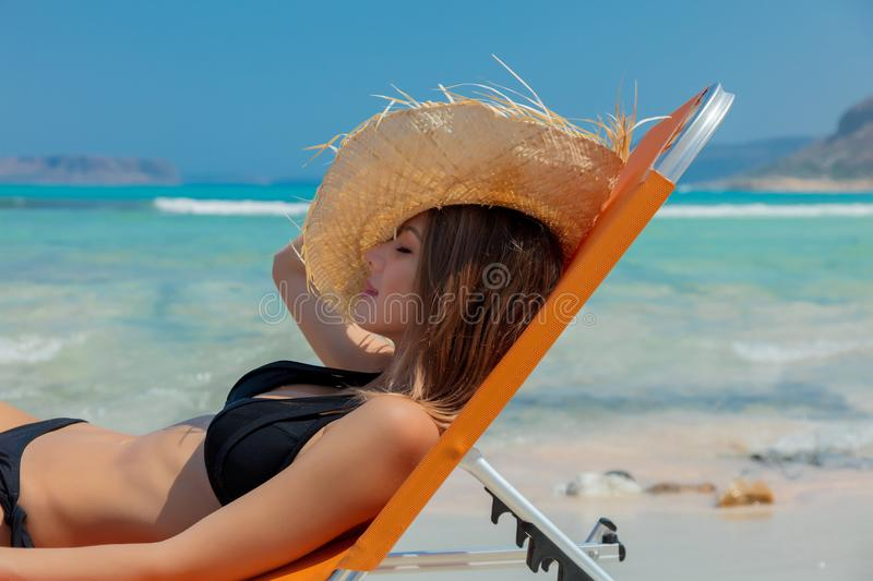 Girl lying down on lounger on Balos beach. Young redhead girl in black bikini and with hat lying down on lounger on Balos beach, west Crete, Greece. Summertime royalty free stock images