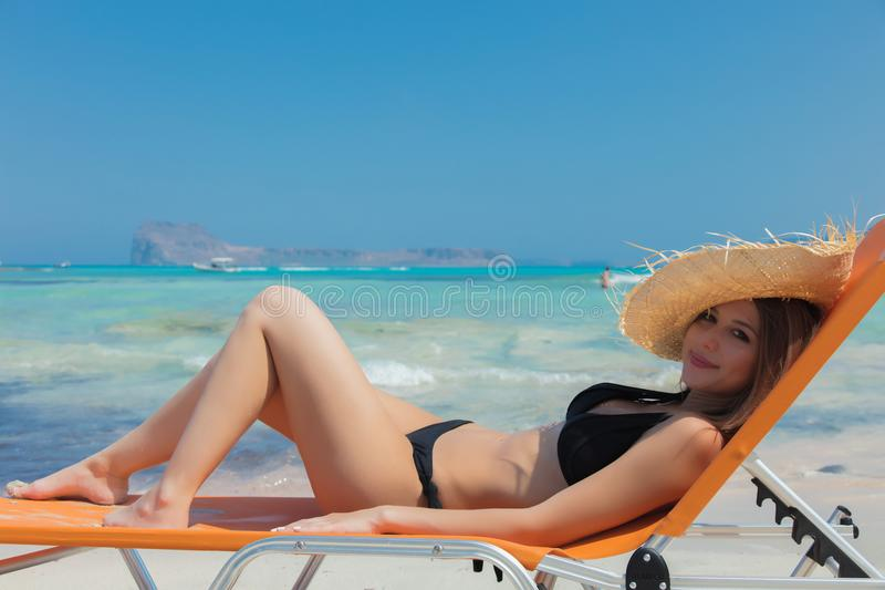 Girl lying down on lounger on Balos beach. Young redhead girl in black bikini and with hat lying down on lounger on Balos beach, west Crete, Greece. Summertime royalty free stock photo