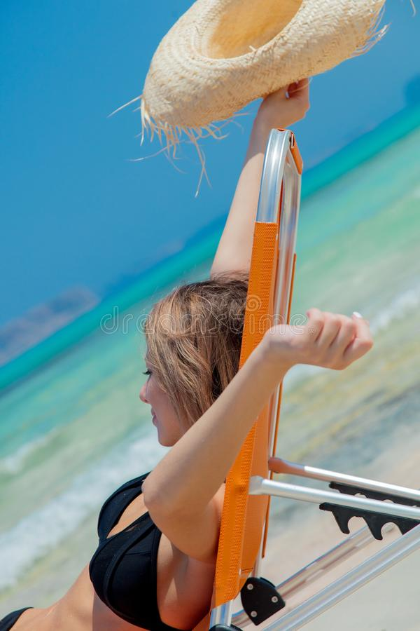 Girl lying down on lounger on Balos beach. Young redhead girl in black bikini and with hat lying down on lounger on Balos beach, west Crete, Greece. Summertime royalty free stock image