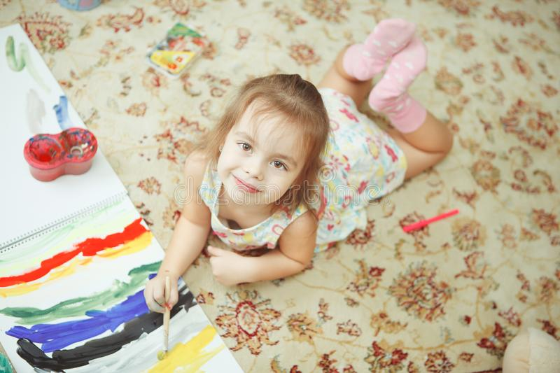 Girl lying on floor on carpet with floral pattern royalty free stock photos