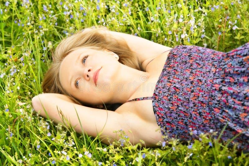 Girl lying in flowers stock image