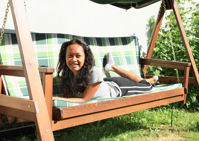 Girl lying on a garden swing royalty free stock image