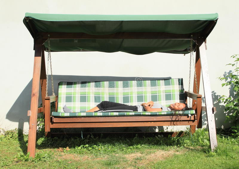 Girl lying on a garden swing royalty free stock photos