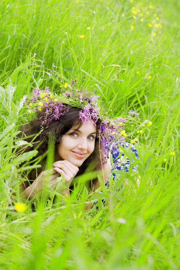 Girl, lying on the grass field. The image of a beautiful girl, lying on the grass field royalty free stock image