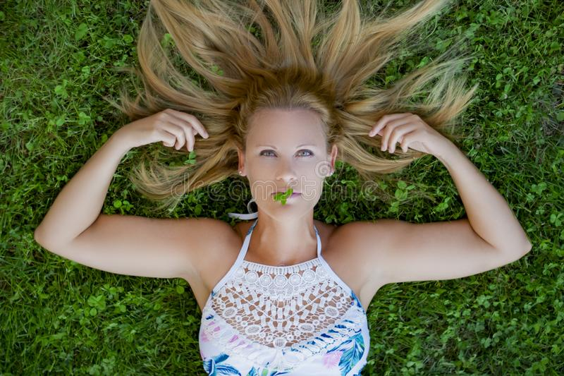 Girl lying on the grass stock photography
