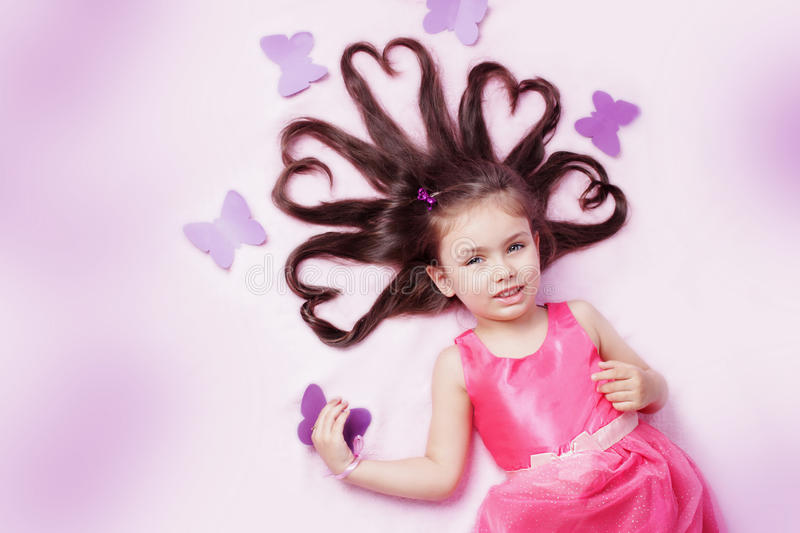 Girl lying with heart shaped hair and butterflies stock image
