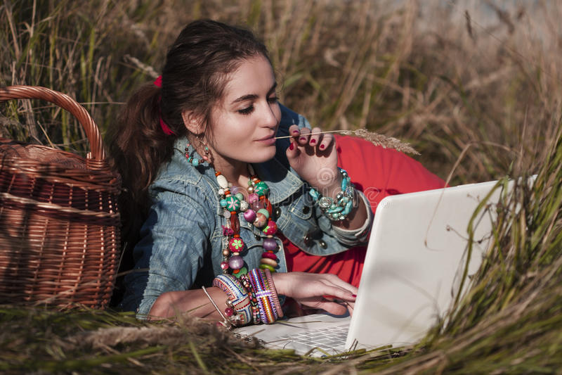 Girl lying at laptop and basket and hold stick with hand and mouth stock image