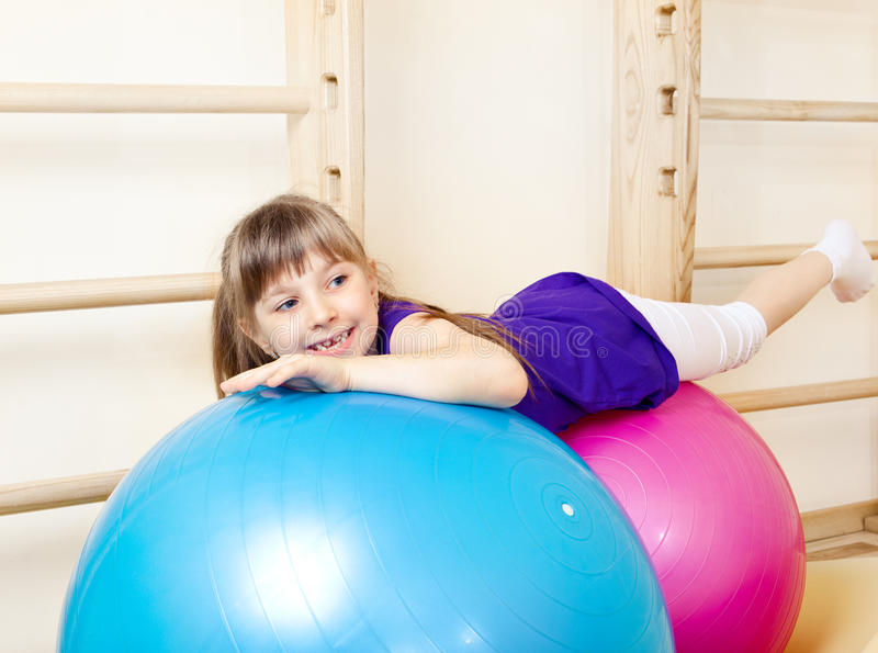 Download Girl Lying On Large Gymnastic Balls Stock Image - Image: 25185269