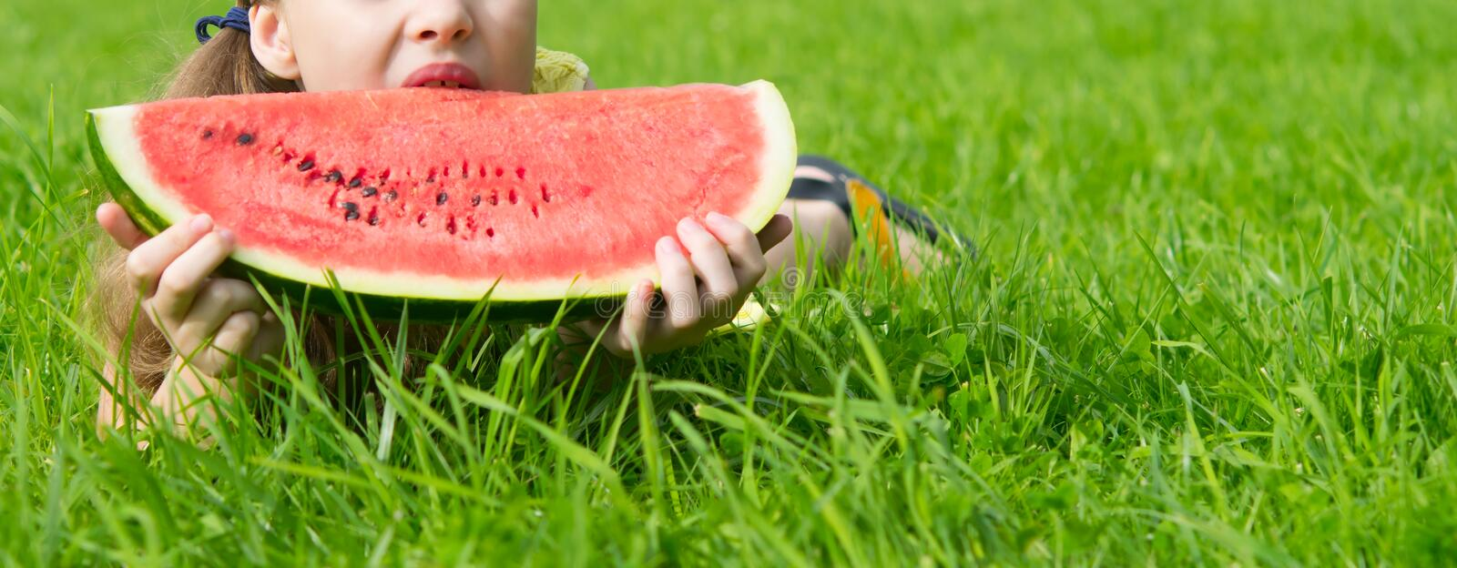 Girl lying on the lawn. and holding a large slice of watermelon on a green background. close up stock photo
