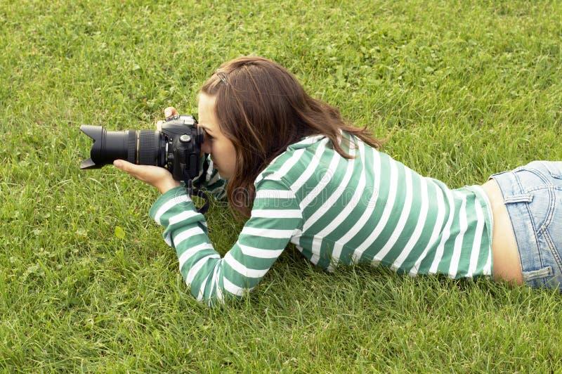 Girl lying with photo camera stock photo