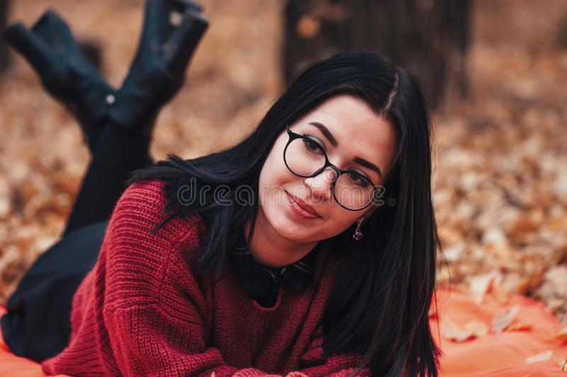 Girl lying on the plaid in autumn forest, nature background royalty free stock photography