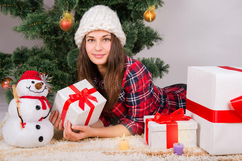 Girl lying between the presents under the Christmas tree royalty free stock photography