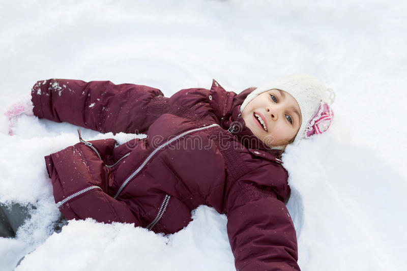 Girl lying in the snow. And smiling stock images