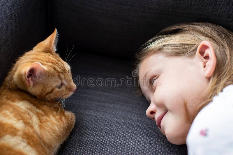 Girl Lying On Sofa At Home Looking Lovingly At Pet Cat. Girl Lying On Sofa At Home Looking Lovingly At Cat stock images