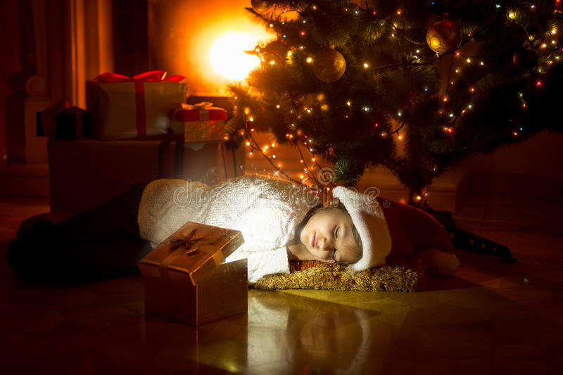 Girl lying under Christmas tree and looking in glowing gift box stock photography