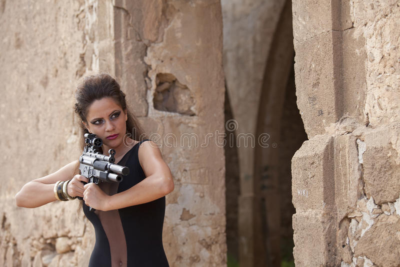 Girl with machine gun. Girl with full make up holding machine gun in old stone ruins royalty free stock photography
