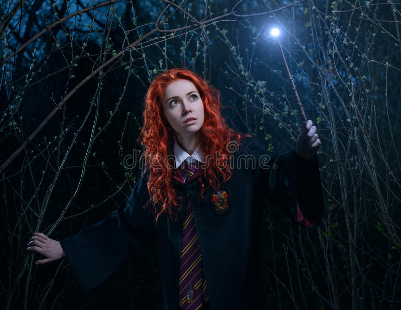 Girl with a magic wand goes through the forest towards the demon stock photos