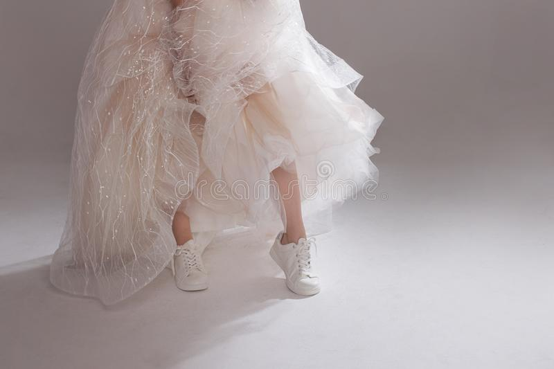 The girl in magnificent wedding dress and white sneakers, legs close-up. Runaway bride stock image