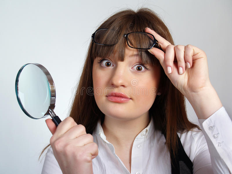 Girl with a magnifier in her hand stock photo
