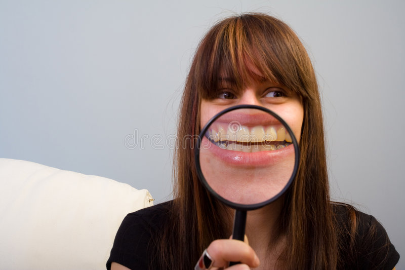Girl and magnifier on mouth stock photo