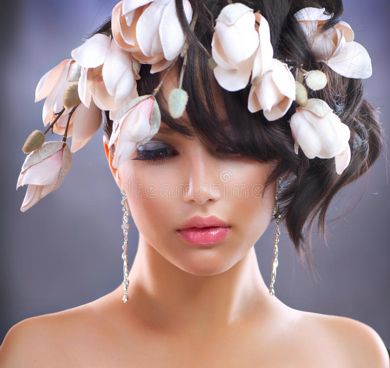 Girl with Magnolia Flowers. Fashion Brunette Girl with Magnolia Flowers. Hairstyle stock image