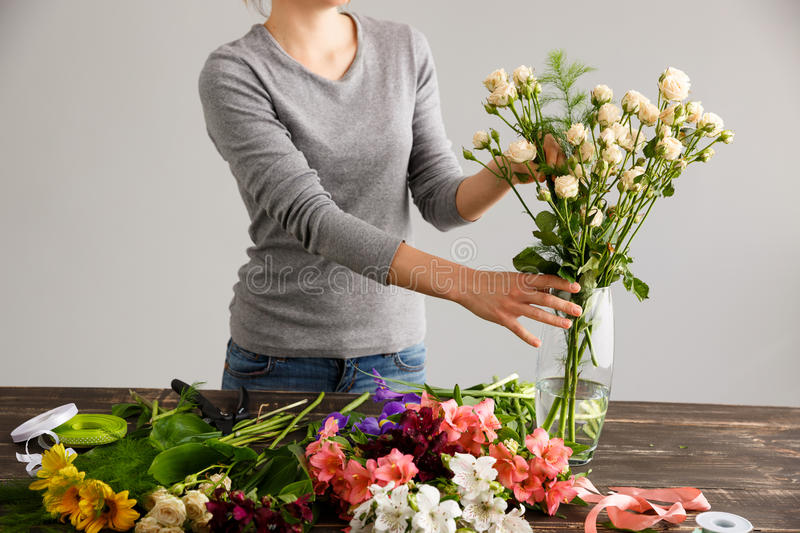 Girl Make Bouquet Over Gray Background Putting Flowers In Vase