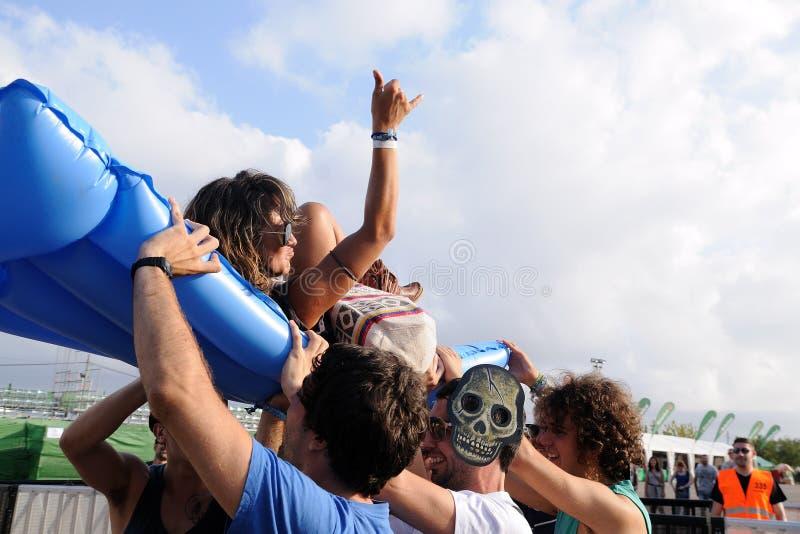 Girl makes body surfing over an inflatable mattress at Los Tiki Phantoms band show at FIB. BENICASSIM, SPAIN - JULY 12: Girl makes body surfing over an stock photos
