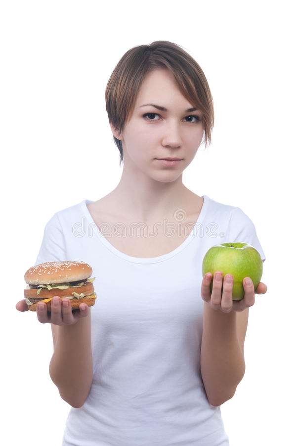 Girl makes choice between apple and hamburger. Isolated on white royalty free stock photo