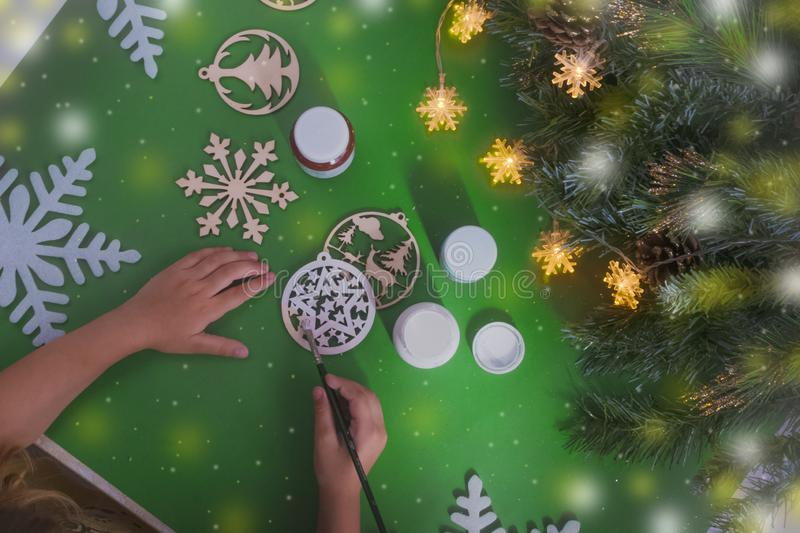 Girl makes Christmas toys, draws white paint balls on the green table next to the green tree.Children& x27;s crafts. creativity. Christmas toy.leisure with royalty free stock images