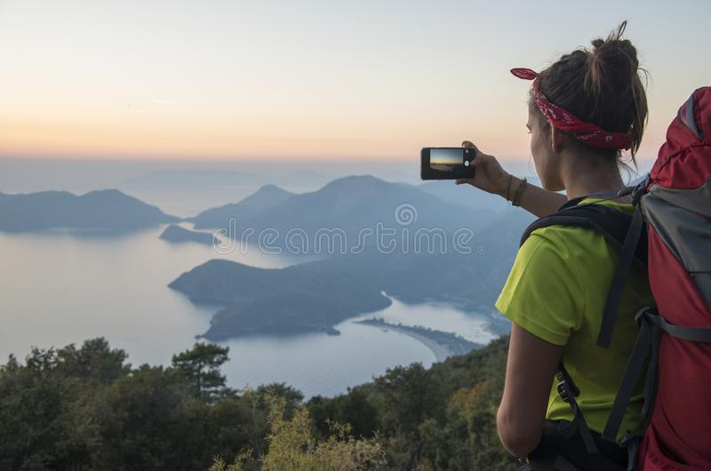 Girl making landscape photo. Girl makes landscape photo with help of smartphone. Landscape contains sundown over sea and mountains. Travel scene, so woman has royalty free stock photo