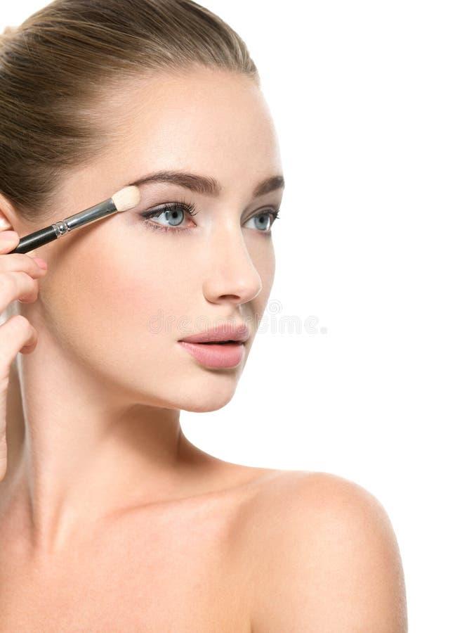 Girl makes makeup. Woman applies makeup shadow on the eyelid royalty free stock image