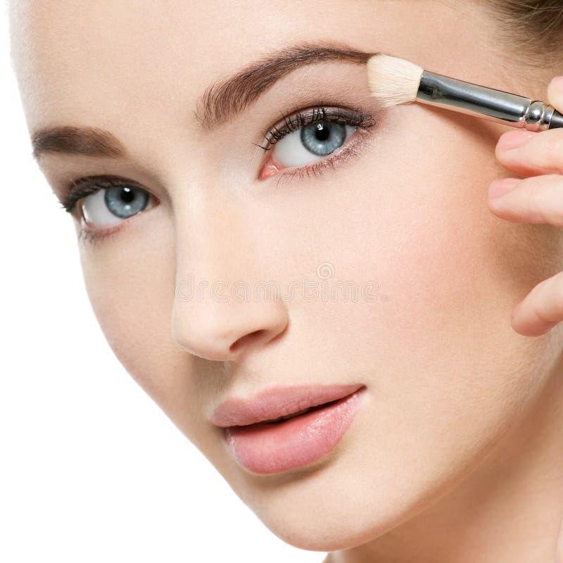 Girl makes makeup. Woman applies makeup shadow on the eyelid stock photos