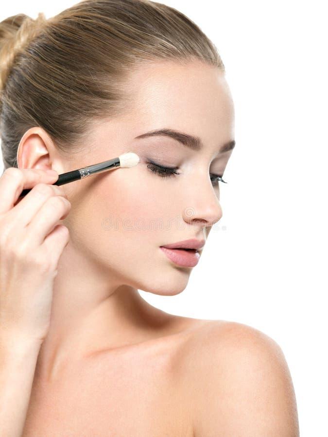 Girl makes makeup. Woman applies makeup shadow on the eyelid stock photo