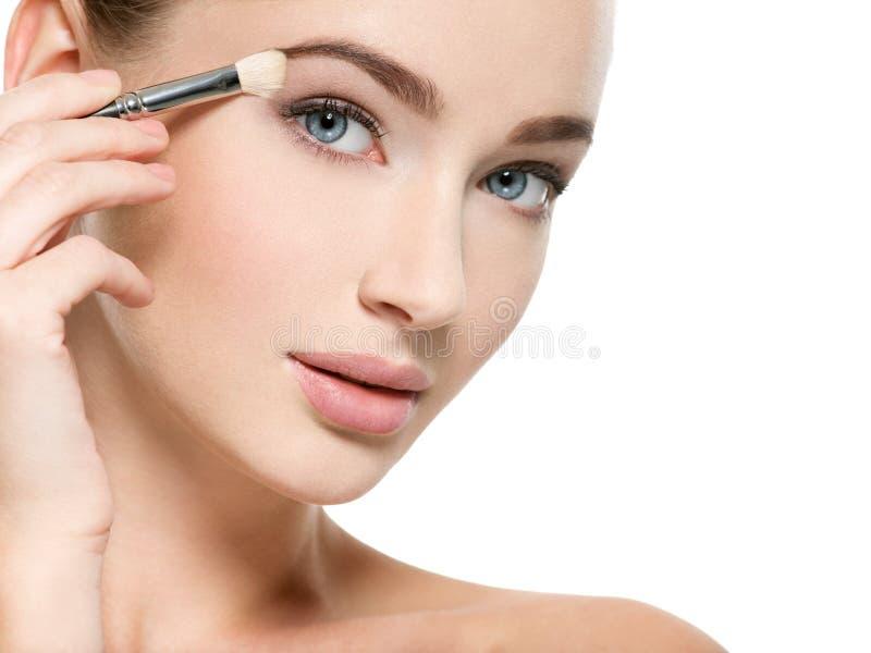 Girl makes makeup. Woman applies makeup shadow on the eyelid stock image
