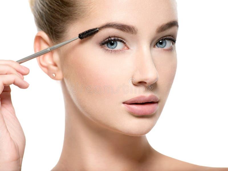 Girl makes makeup. Woman apply mascara on eyelashes royalty free stock image
