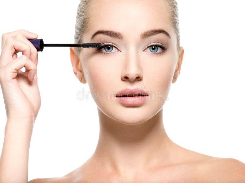 Girl makes makeup. Woman apply mascara on eyelashes royalty free stock photography