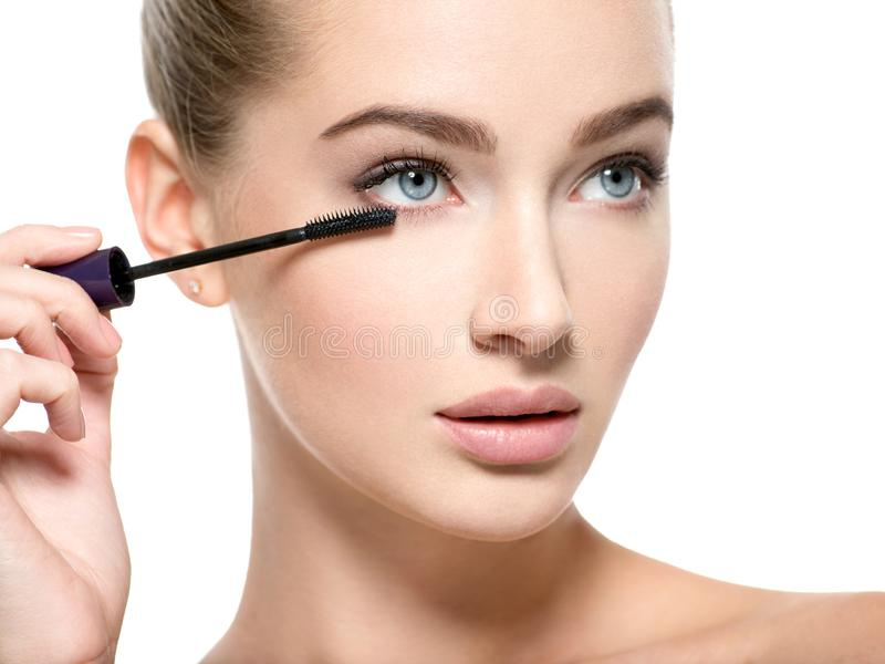 Girl makes makeup. Woman apply mascara on eyelashes royalty free stock images