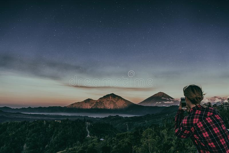 The girl makes a photo on the phone of the mountain volcano Batur on background night sky with stars. Silhouette of the mountain volcano Batur on background stock photos