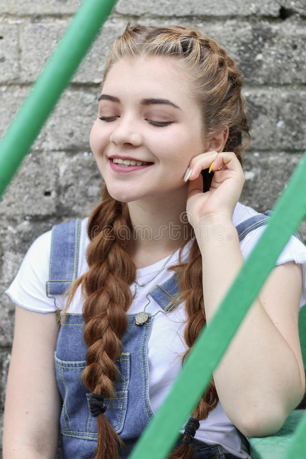 The girl makes preparing for painting a wooden surface gazebo, fence stock image