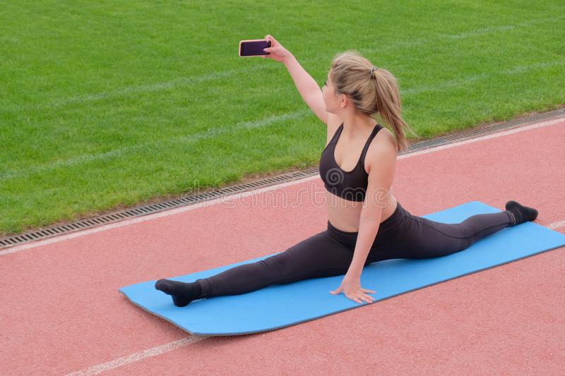 The girl makes a selfie sitting on the twine. Stretching classes in the fresh air. Gymnastics Stretching of the feet royalty free stock photography